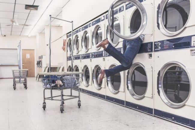 コインランドリーの洗濯機に体を突っ込んでいる人
