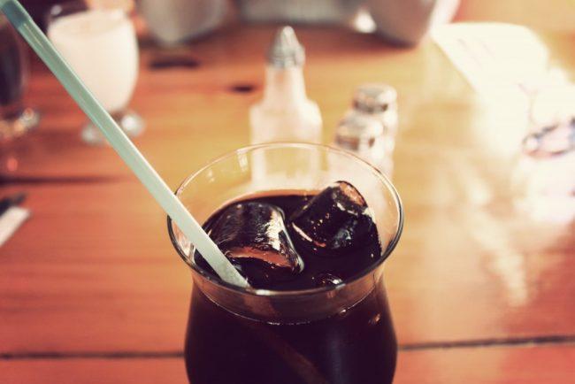 テーブルの上に置いてある、氷の入った冷えたコーラ