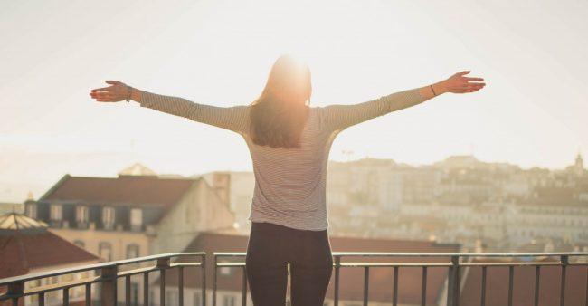 バルコニーで両手を広げて景色を見ている女性